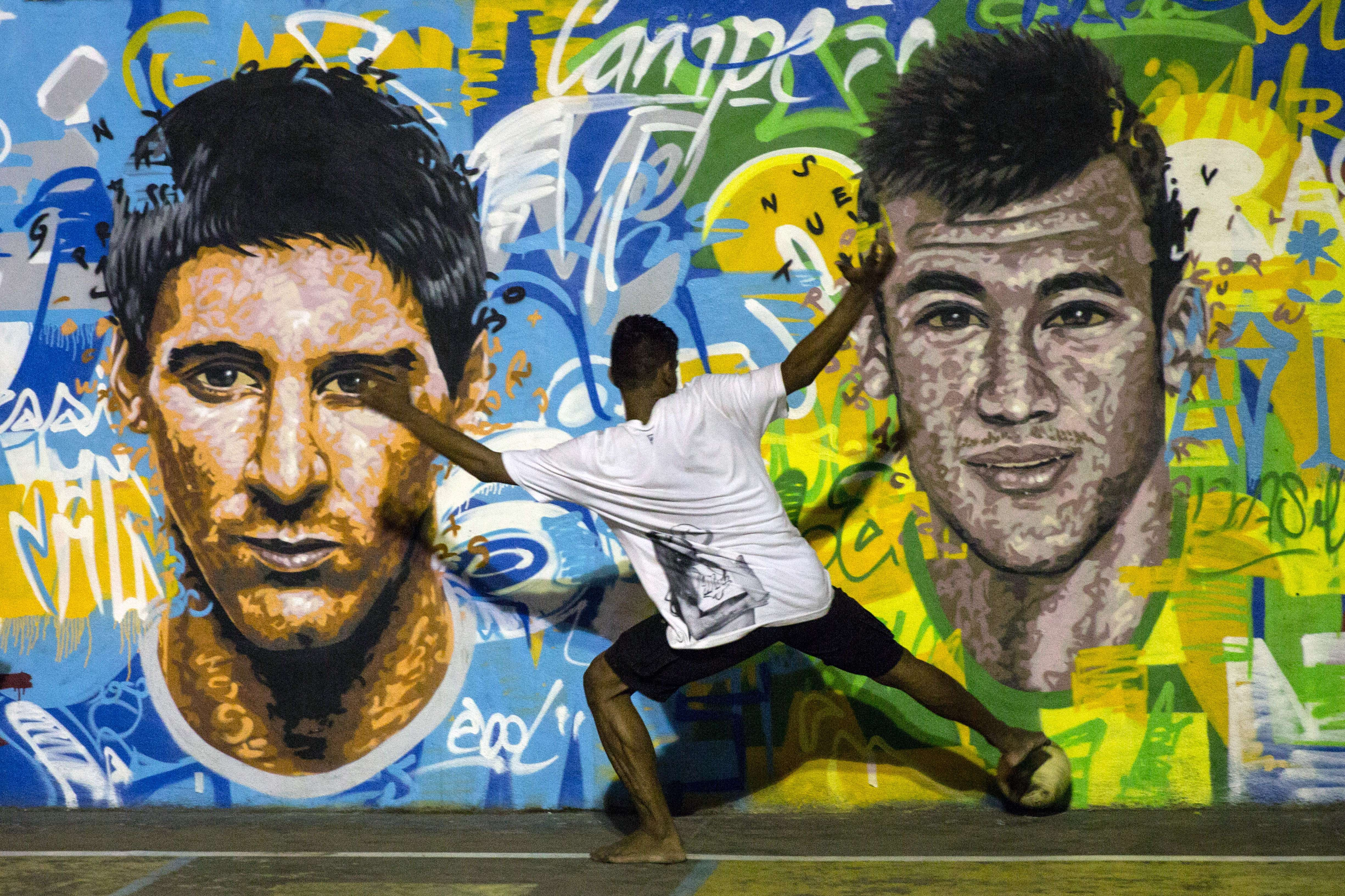 TOPSHOTS-Youngsters play football in front of a mural of Argentine fo